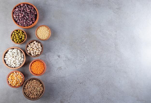 Tigelas de barro cheias de lentilhas cruas, ervilhas e feijão na superfície da pedra