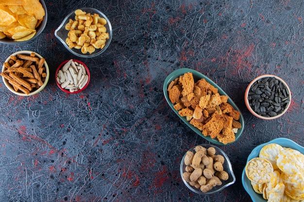 Tigelas de batatas fritas crocantes, biscoitos e sementes de girassóis na superfície escura.