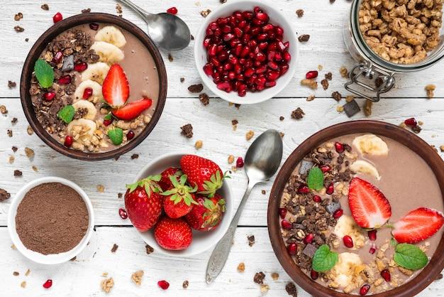 Tigelas de batido de proteína de cacau ou chocolate e banana com sementes de granola, morango e romã, servidas no café da manhã