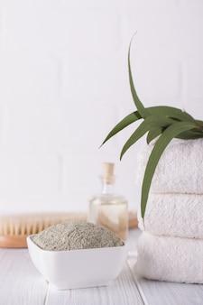 Tigelas de cerâmica com pó de argila verde e folhas frescas de eucalipto. conceito de cuidados com o rosto e corpo.