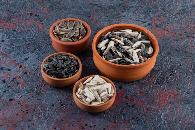Tigelas de cerâmica com sementes de girassóis crocantes na superfície escura.