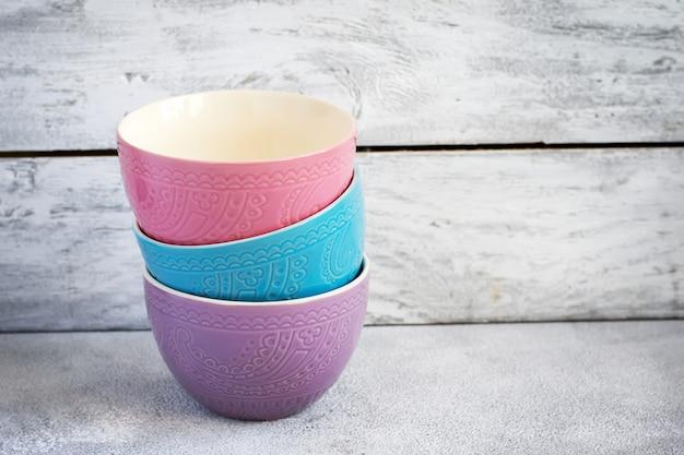 Tigelas de cerâmica pastel coloridas sobre fundo branco, cópia espaço