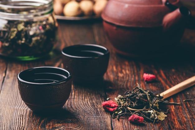 Tigelas de chá de ferro fundido com bule e colher de pau de chá de ervas de framboesa