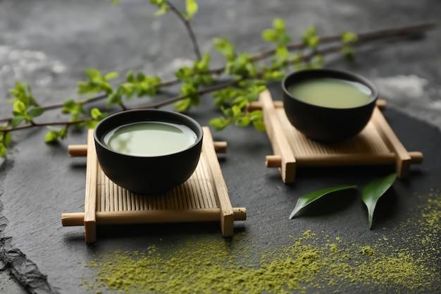 Tigelas de chá matcha fresco no prato de ardósia