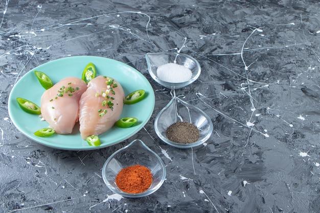 Tigelas de especiarias e peito de frango em um prato, na superfície de mármore.
