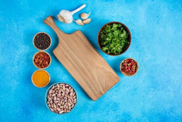 Tigelas de feijão cru e especiarias orgânicas sobre fundo azul.