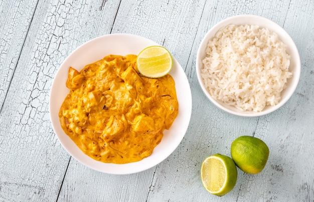 Tigelas de frango ao curry e arroz branco cozido