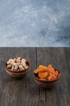 Tigelas de frutas secas de damasco saudáveis e amendoim com casca em uma mesa de madeira.