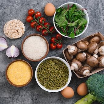 Tigelas de grãos de arroz; brotos de feijão; polenta com legumes frescos; ovos e bolo de arroz tufado no pano de fundo texturizado cinza