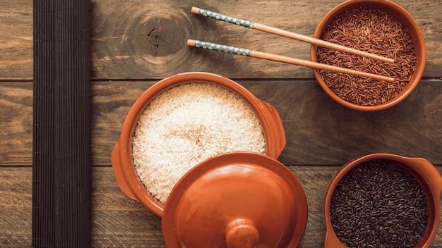 Tigelas de grãos de arroz cru com pauzinhos na mesa de madeira