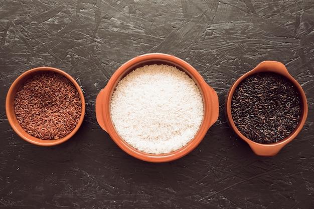 Tigelas de grãos de arroz orgânico em plano de fundo texturizado cinzento