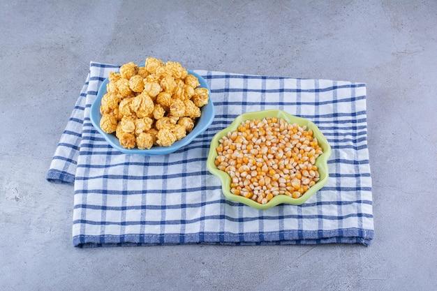 Tigelas de grãos de milho e pipoca revestida de caramelo em uma toalha na superfície de mármore