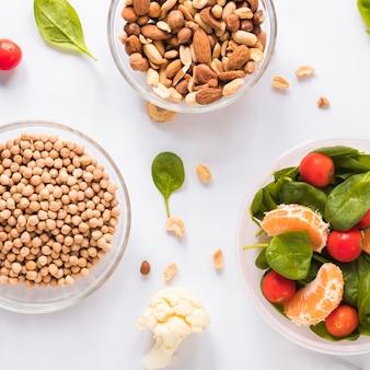 Tigelas de ingredientes saudáveis sobre fundo branco