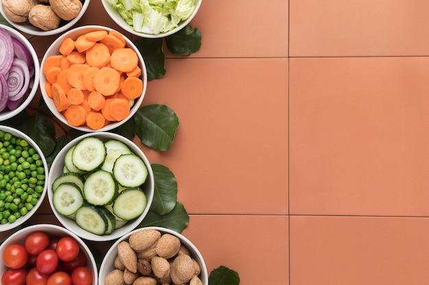 Tigelas de legumes fatiados copiam o espaço