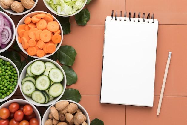 Tigelas de legumes fatiados e bloco de notas