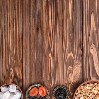 Tigelas de lukum; nozes e frutas secas no fundo de madeira com espaço da cópia para escrever o texto