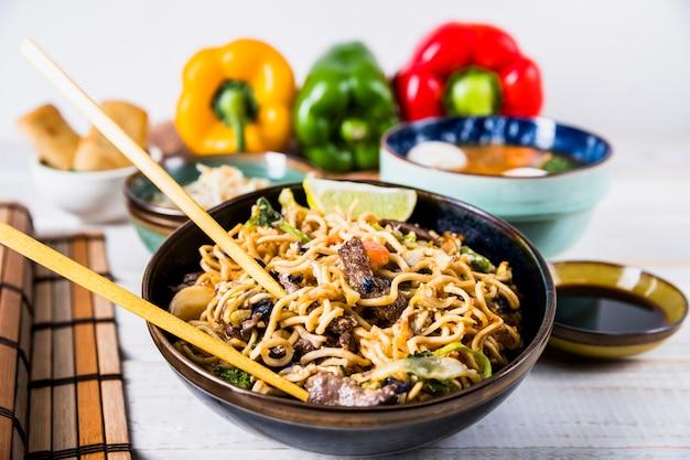 Tigelas de macarrão udon com carne e pimentão na mesa branca