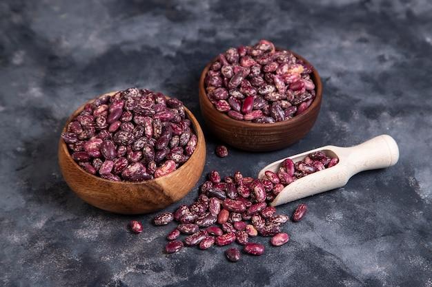 Tigelas de madeira cheias de grãos crus de feijão seco