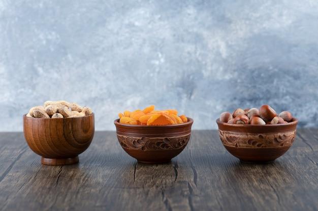 Tigelas de madeira cheias de nozes saudáveis com frutas secas de damasco na mesa de madeira.