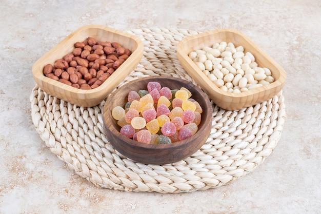 Tigelas de madeira com balas doces e grãos de amendoim na superfície de mármore.