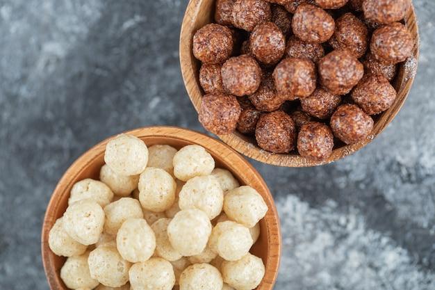 Tigelas de madeira com bolas de milho doce em cinza.