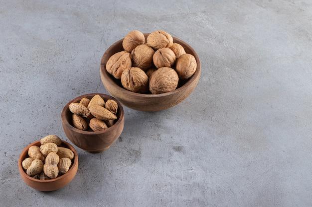 Tigelas de madeira com nozes, amêndoas e amendoins com casca orgânica em fundo de pedra.