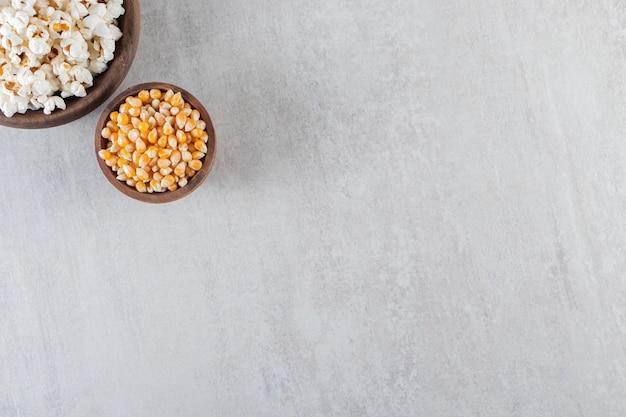 Tigelas de madeira com pipoca e grãos de milho crus na mesa de pedra.