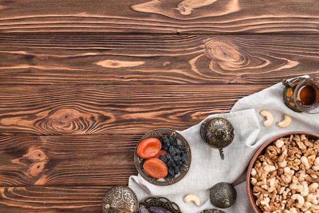 Tigelas de nozes mistas de barro; copo de chá e frutas secas na toalha de mesa sobre a mesa de madeira
