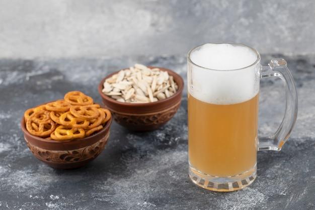 Tigelas de pretzels salgados e sementes de girassol com caneca de cerveja na superfície de mármore