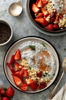 Tigelas de pudim de sementes de chia com morangos e aveia. café da manhã com comida saudável, vista de cima. cena de comida.