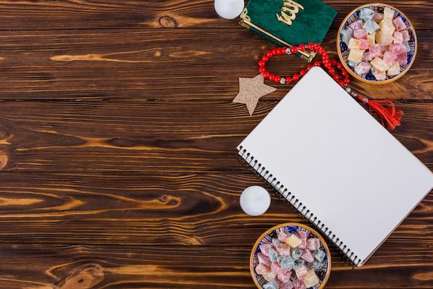 Tigelas de rakhat-lukum multicoloridas; vela; kuran; contas vermelhas e caderno longo espiral na mesa de madeira