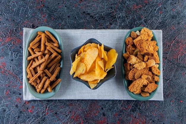 Tigelas de saborosas batatas fritas e biscoitos crocantes na superfície escura.