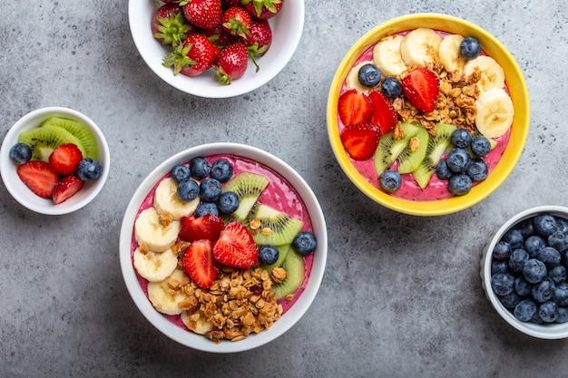 Tigelas de smoothie de açaí de verão com morangos, banana, mirtilos, kiwis e granola em fundo cinza de concreto. taça de café da manhã com frutas e cereais, close-up, vista de cima, comida saudável