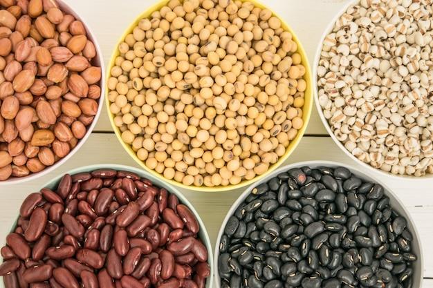 Tigelas de soja, feijão preto, ler feijão, amendoim e milho na mesa branca.