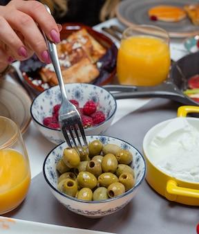 Tigelas de suco de laranja com azeitona e framboesa e panquecas embrulhadas
