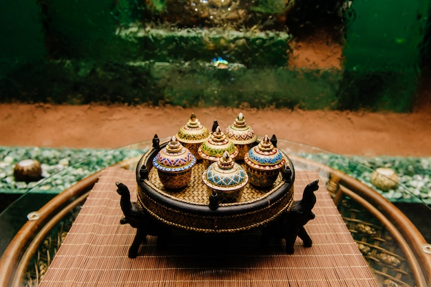 Tigelas decorativas tailandesas na placa de vime
