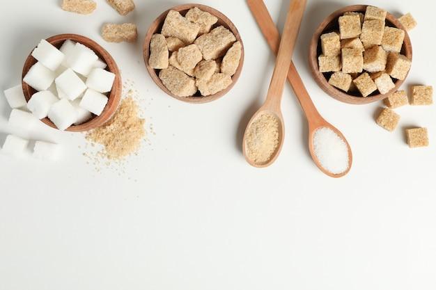 Tigelas e colheres com açúcar no fundo branco, vista superior