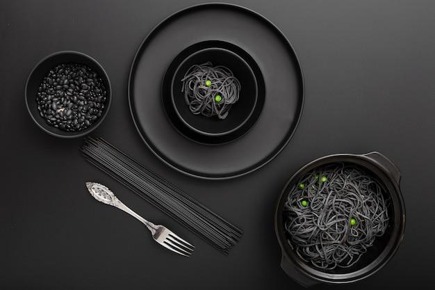 Tigelas escuras com macarrão e feijão em uma mesa preta
