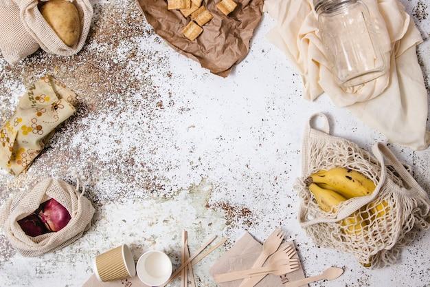 Tigelas, pratos, copos, garfos, guardanapos, diferentes utensílios de mesa sem plástico, sacola de compras, vasilha de vidro e abelhas reutilizáveis exibidas em torno de uma mesa com diferentes ingredientes, café e leite