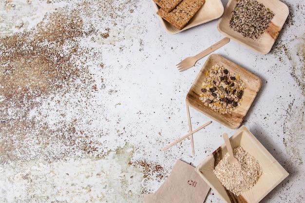 Tigelas, pratos, garfos, guardanapos e diferentes utensílios de mesa sem plástico exibidos no lado direito de uma mesa com diferentes ingredientes.