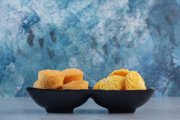 Tigelas pretas de mini bolos doces e biscoitos sobre fundo azul.