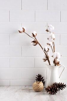Tijolo branco brilhante com flor de algodão em um jarro de pinho e cordão copie o espaço para texto com retrô