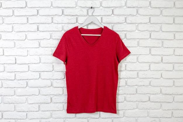 Tijolo caiado de parede com t-shirt no cabide