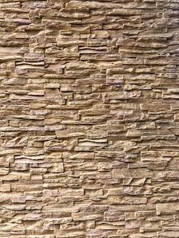 Tijolo clássico aleatório marrom claro disposto na parede para decorar o exterior do edifício.