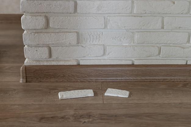 Tijolo de gesso decorativo arrancado da parede interna da casa e caiu na parede danificada horizontal
