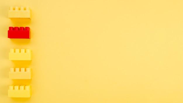 Tijolo de lego vermelho com amarelos e espaço de cópia
