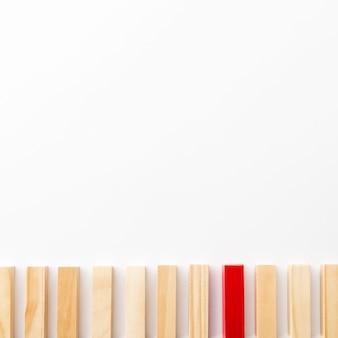 Tijolo de madeira vermelho, rodeado por normais, com espaço de cópia