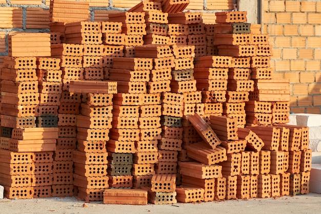 Tijolo vermelho empilhado ordenadamente em linhas para a construção de um edifício residencial