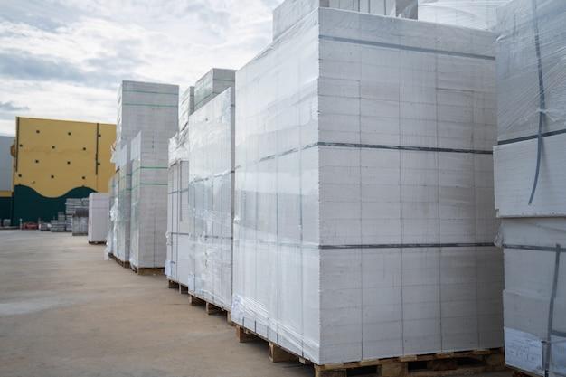 Tijolos de bloco de concreto colocados em paletes de madeira no armazém.