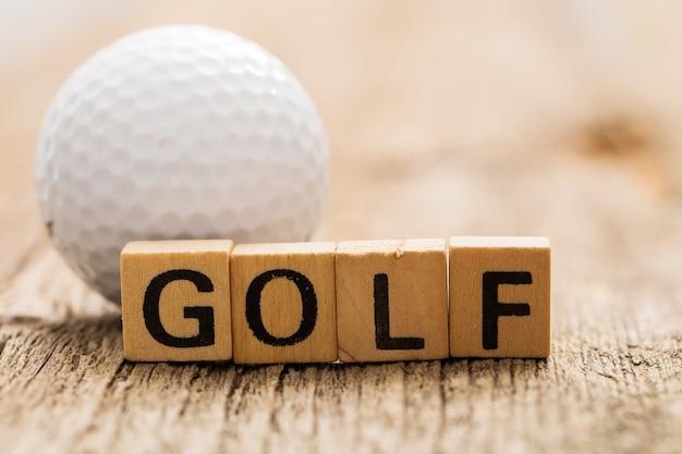 Tijolos de brinquedo na mesa com a palavra golf e bola de golfe